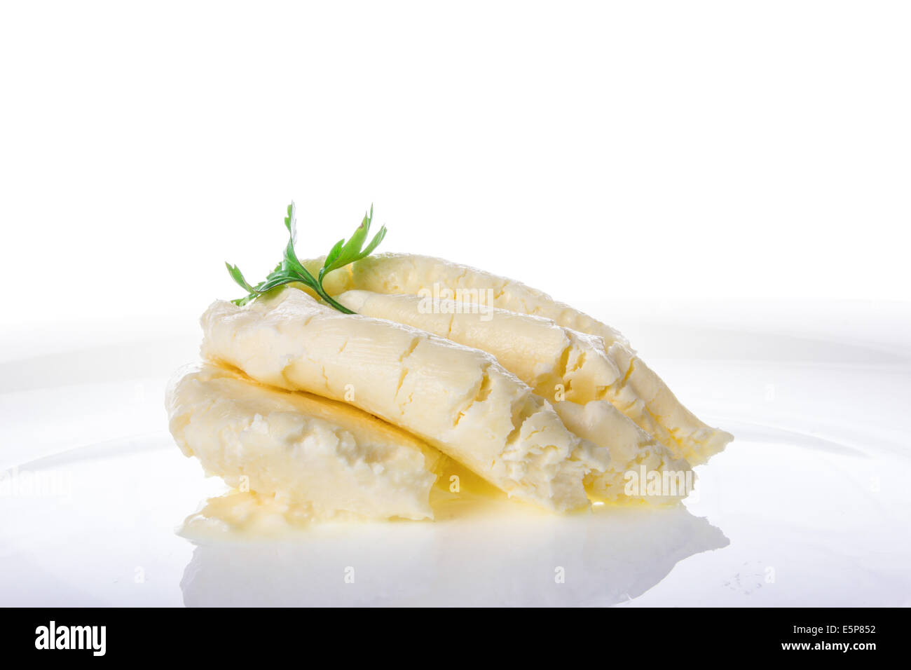 cream cheese milk product portion on white plate with parsley on top; soft cheese cream - Stock Image