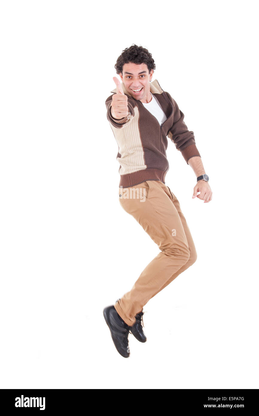 Ecstatic young casual man showing thumbs up jumping of joy and excitement, Successful proud modern guy leaping with - Stock Image