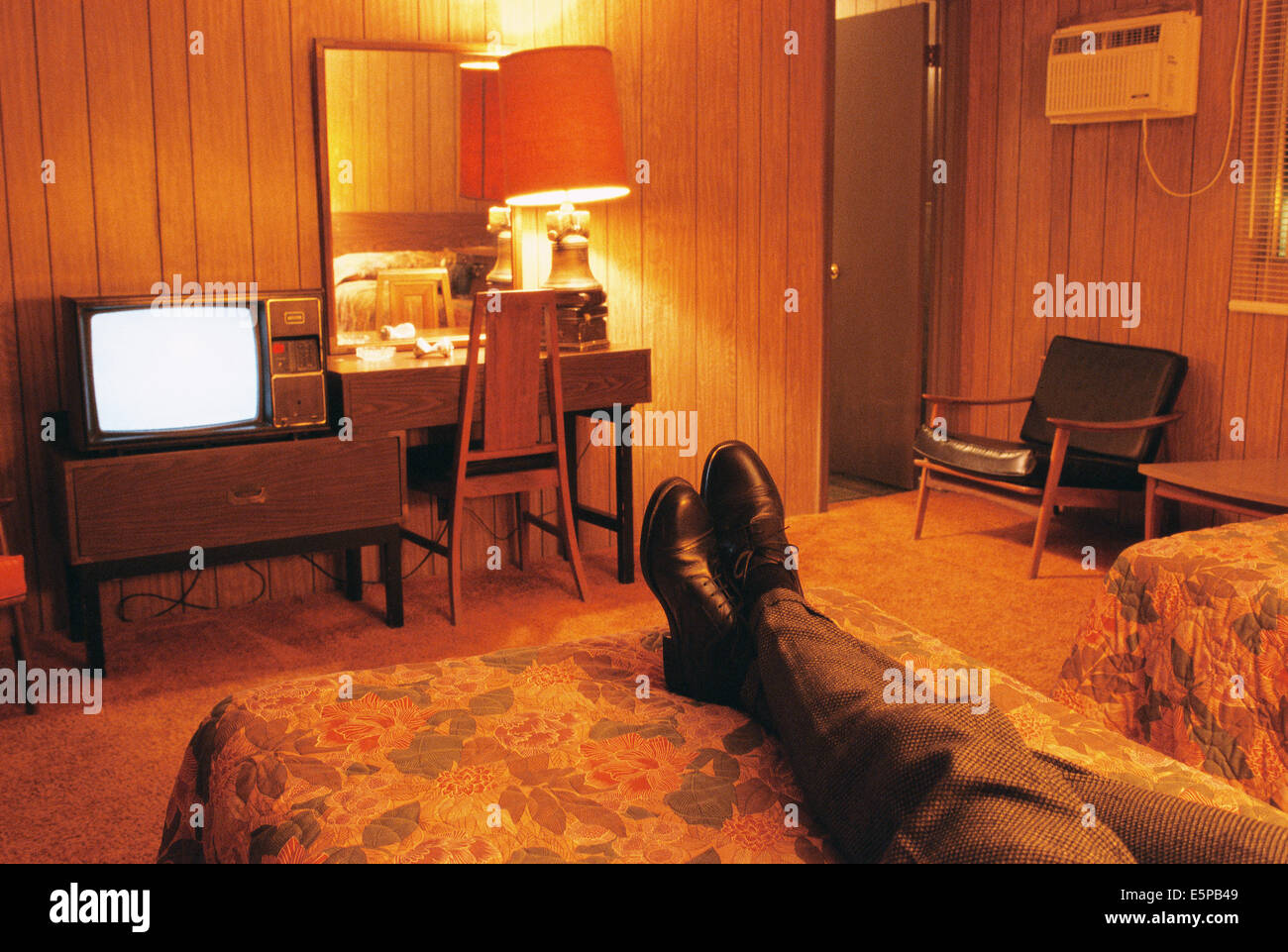 Person watching television in cheap motel - Stock Image