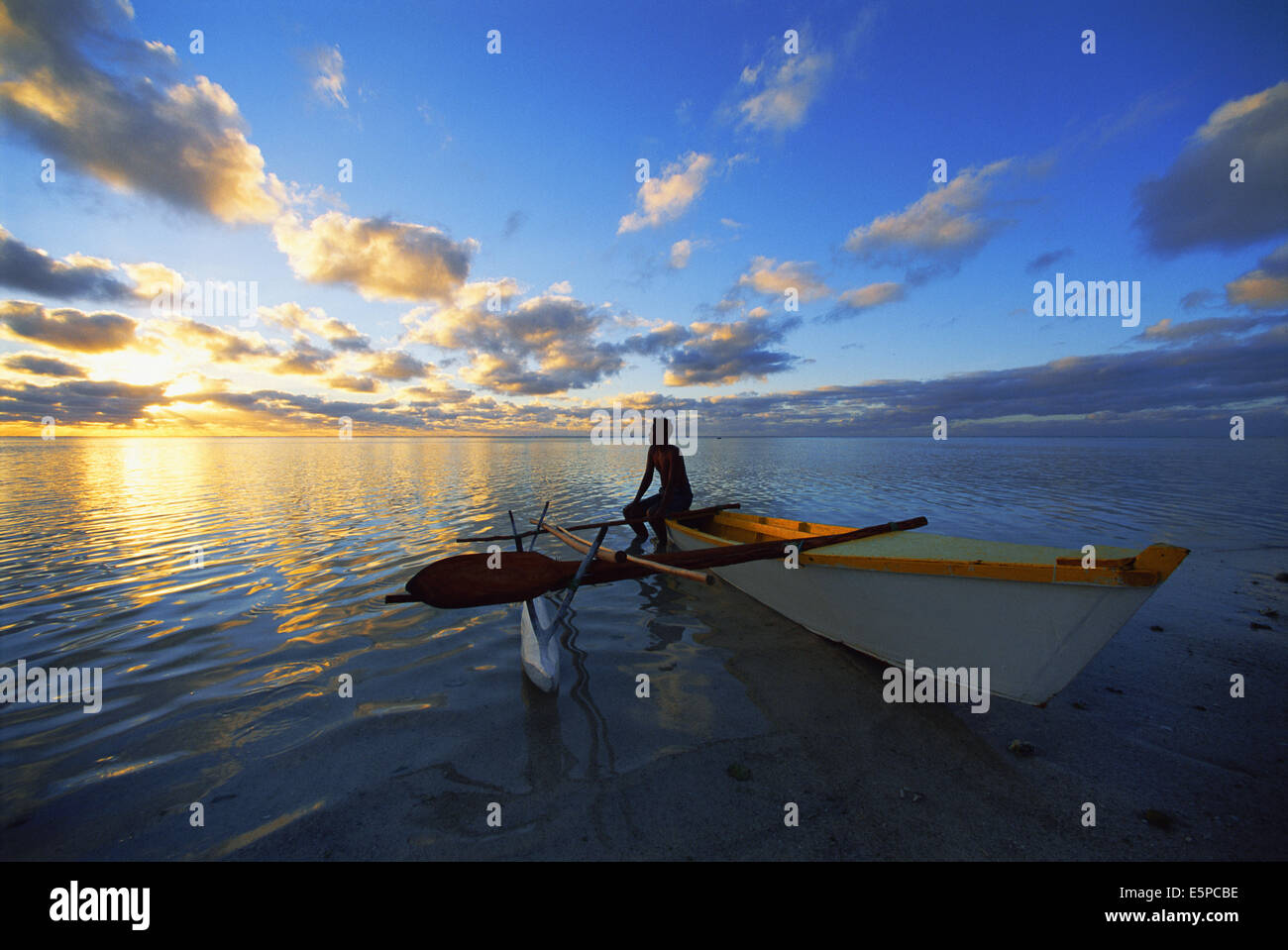 Person sitting on a canoe in Aitutaki, Cook Islands - Stock Image
