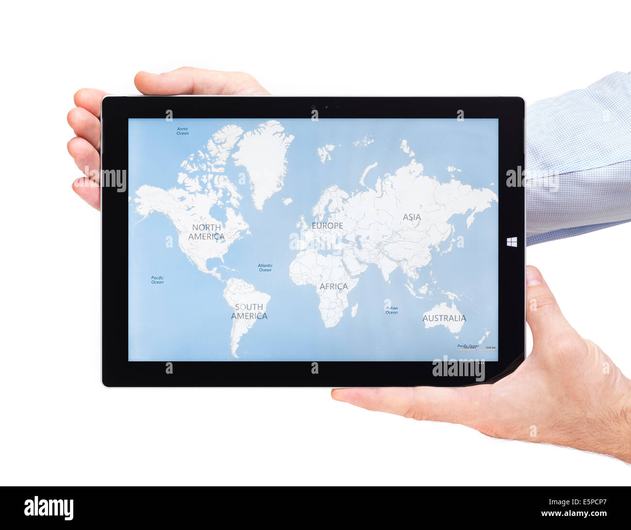 Person hands holding Microsoft Surface Pro 3 tablet computer with world map on its display isolated on white background - Stock Image