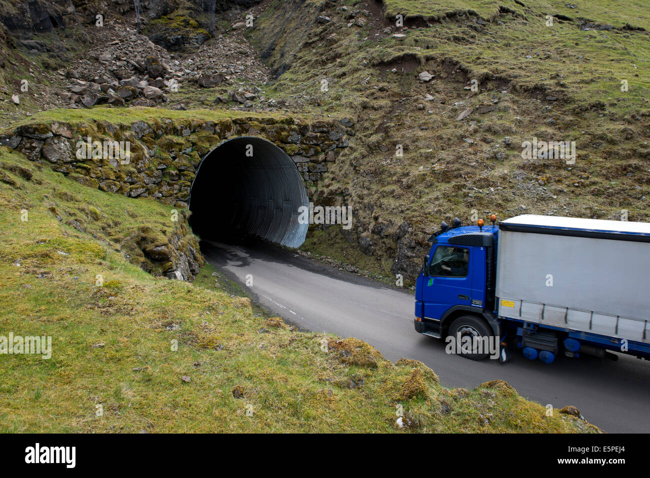 Truck driving into a single-track tunnel between Husar and Mikladalur, Kalsoy, Faroe Islands, Denmark Stock Photo