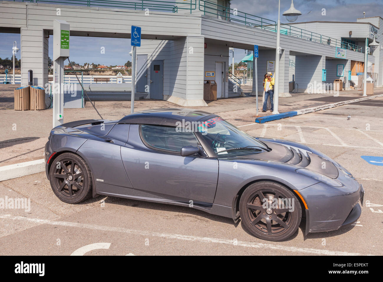Tesla Roadster plugged in to a public re-charging point on the pier at Santa Cruz, California. - Stock Image