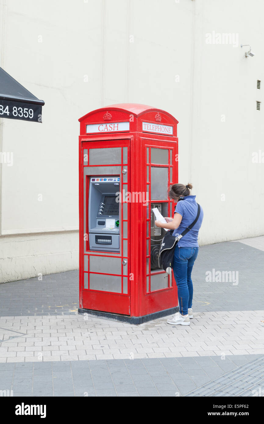 Telephone box converted into an ATM cashpoint and public telephone, London, UK - Stock Image