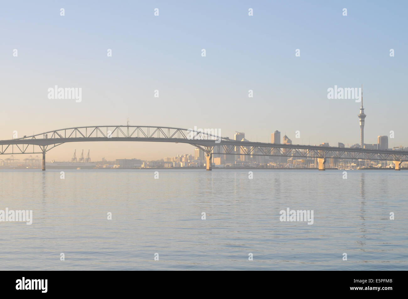 View of Auckland Harbour Bridge from Birkenhead wharf in early morning light with cbd in background - Stock Image