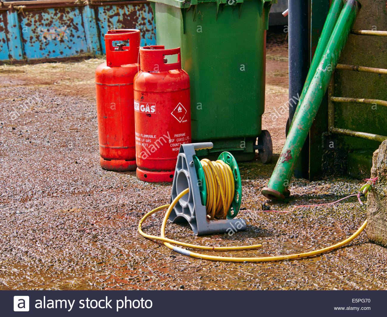two red propane gas bottles and a yellow hosepipe reel on a farmyard uk - Stock Image