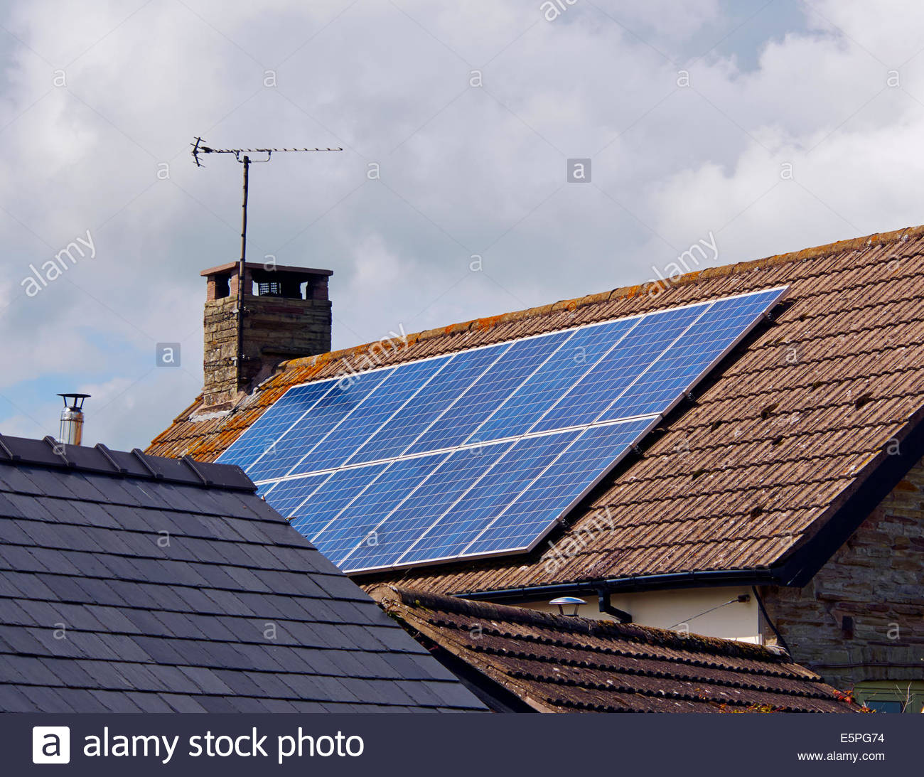 solar energy panels on the roof of a residential building to generate eco friendly electricity - Stock Image