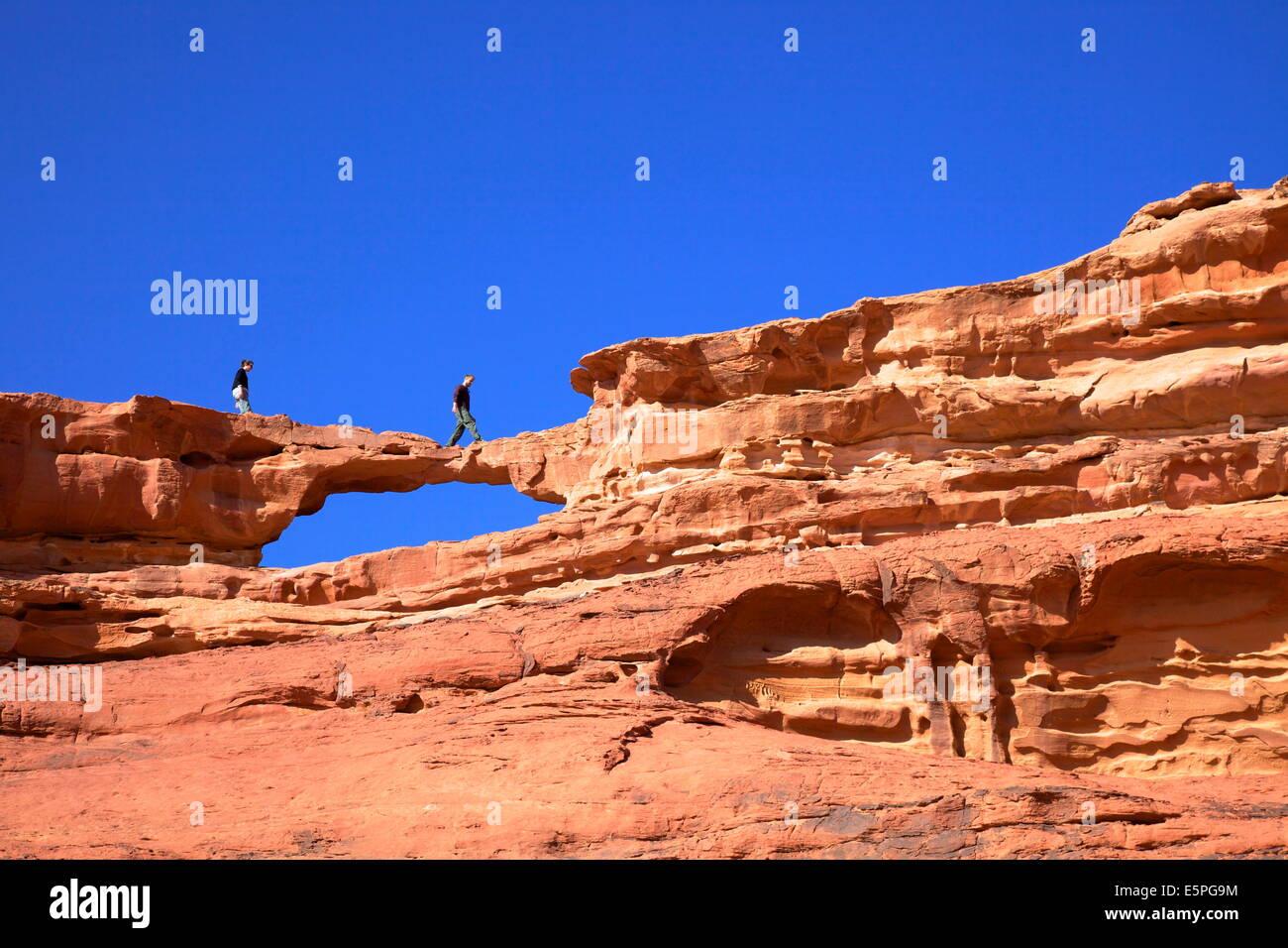 Tourists climbing at Wadi Rum, Jordan, Middle East - Stock Image