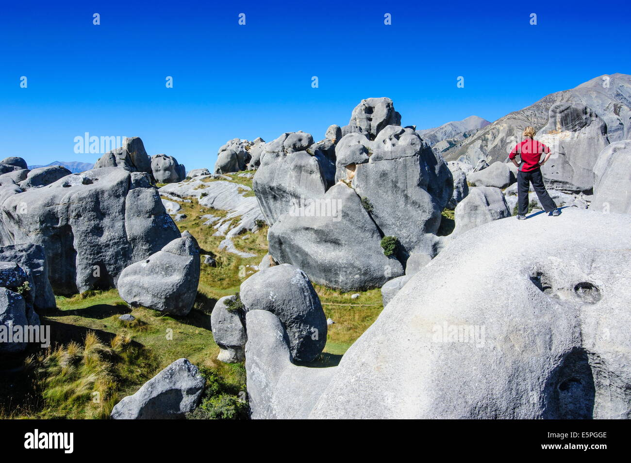 Woman standing on the limestone outcrops of Castle Hill, Canterbury, South Island, New Zealand, Pacific Stock Photo