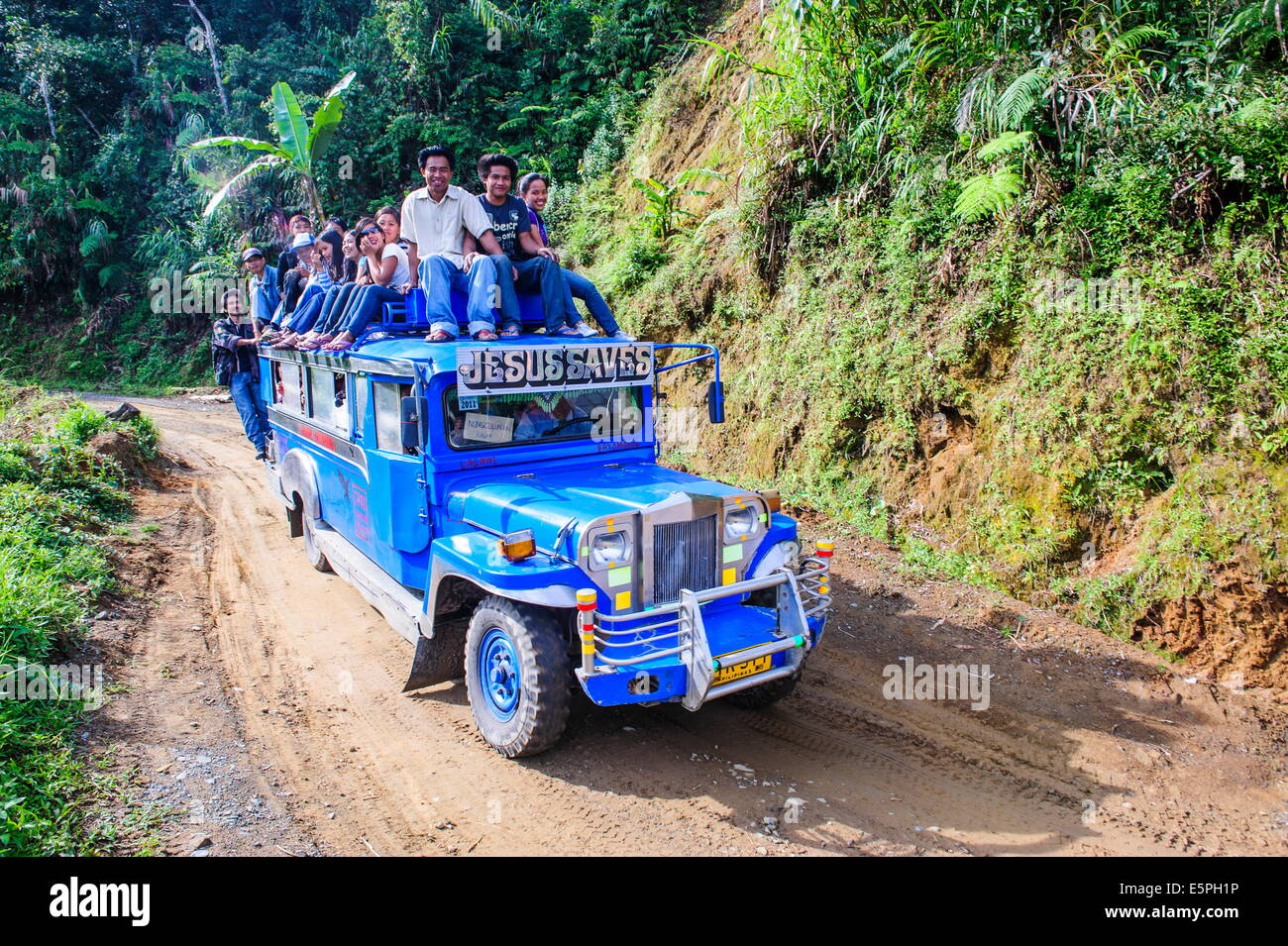 People sitting on a the roof of a jeepney driving through the Hapao rice terraces, Banaue, UNESCO Site, Luzon, Philippines - Stock Image