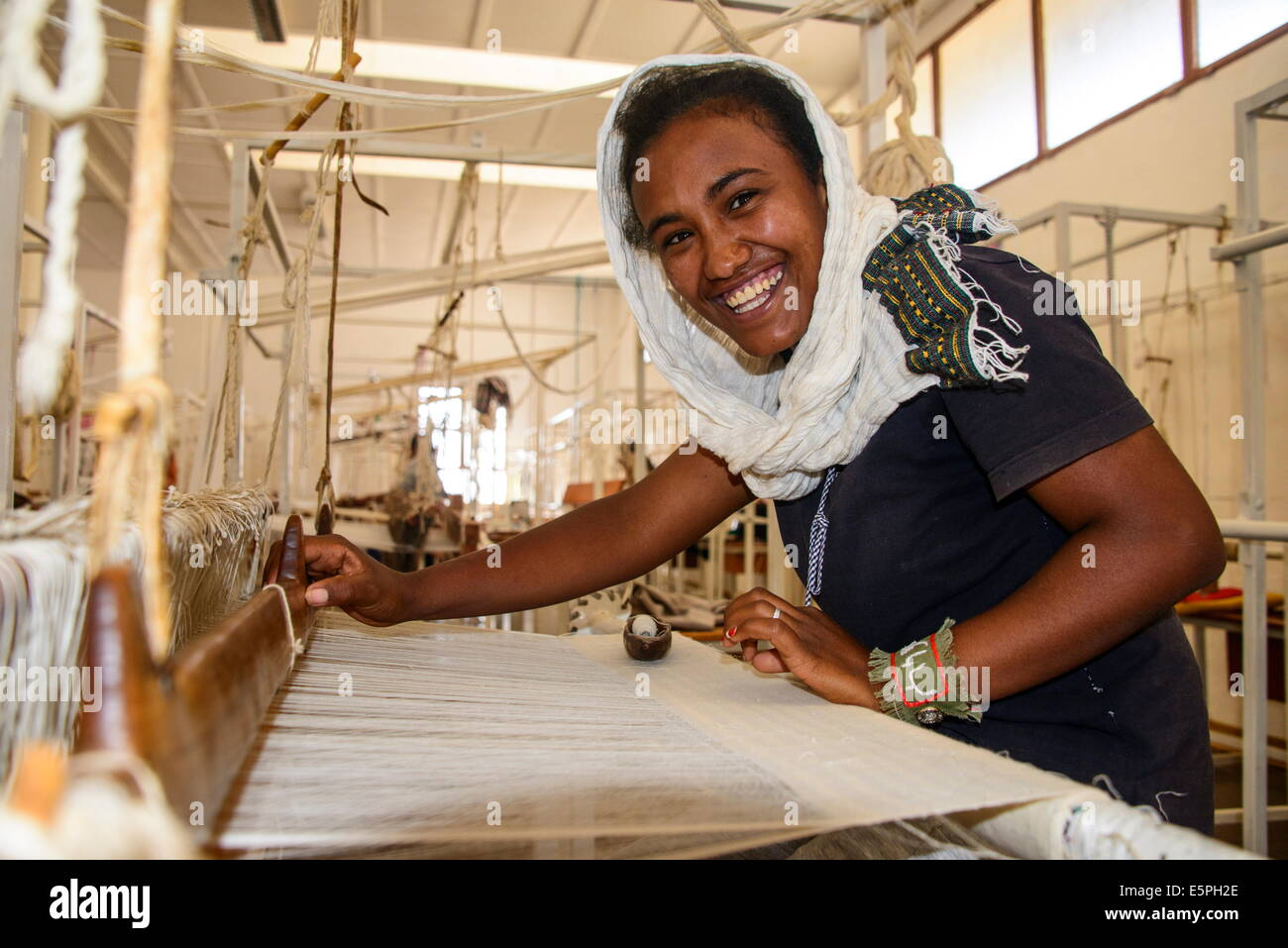 Friendly woman working on a hand weaving loom on a social project in the highlands of Eritrea, Africa - Stock Image