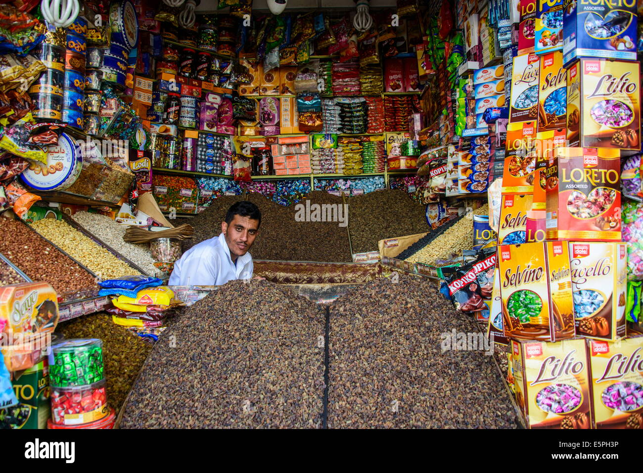 Man sitting in his full shop in the Old Town, UNESCO World Heritage Site, Sanaa, Yemen, Middle East - Stock Image