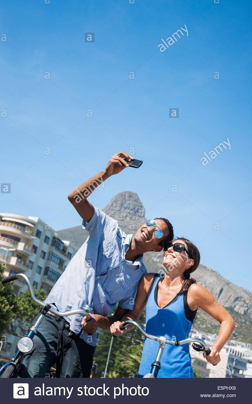 Man and woman couple taking a Selfie photo in front of Lion's Head mountain at Camp's Bay beach, Cape Town, - Stock Image