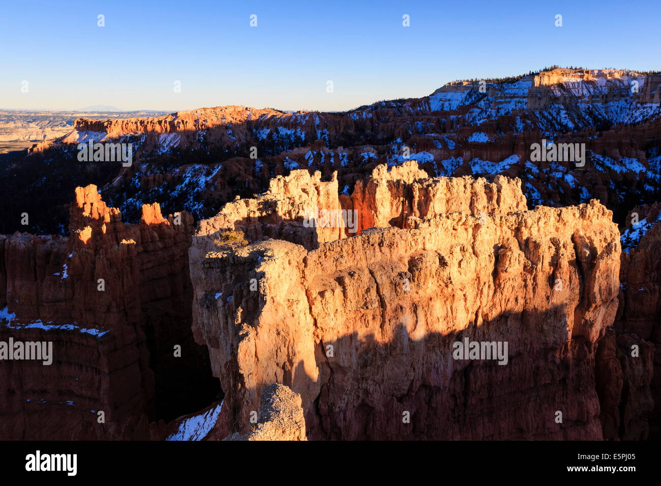 Rocks lit by late afternoon sun with snow, from Sunset Point, Bryce Canyon National Park, Utah, United States of - Stock Image