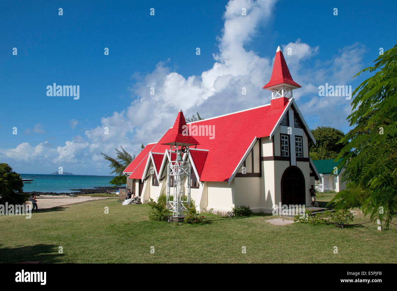 A newly wed couple posing for photos outside the red roofed church at Cap Malheureux on the northwest coast of Mauritius - Stock Image