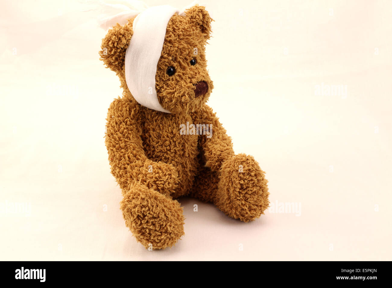 Cute bear toy with toothache bandage on a white background - Stock Image