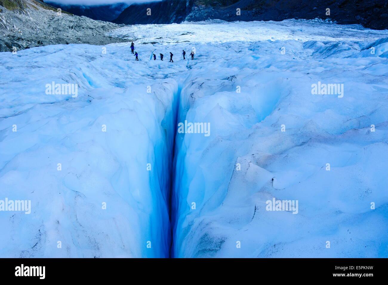 Tourists hiking above a giant crack on Fox Glacier, Westland Tai Poutini National Park, South Island, New Zealand, - Stock Image