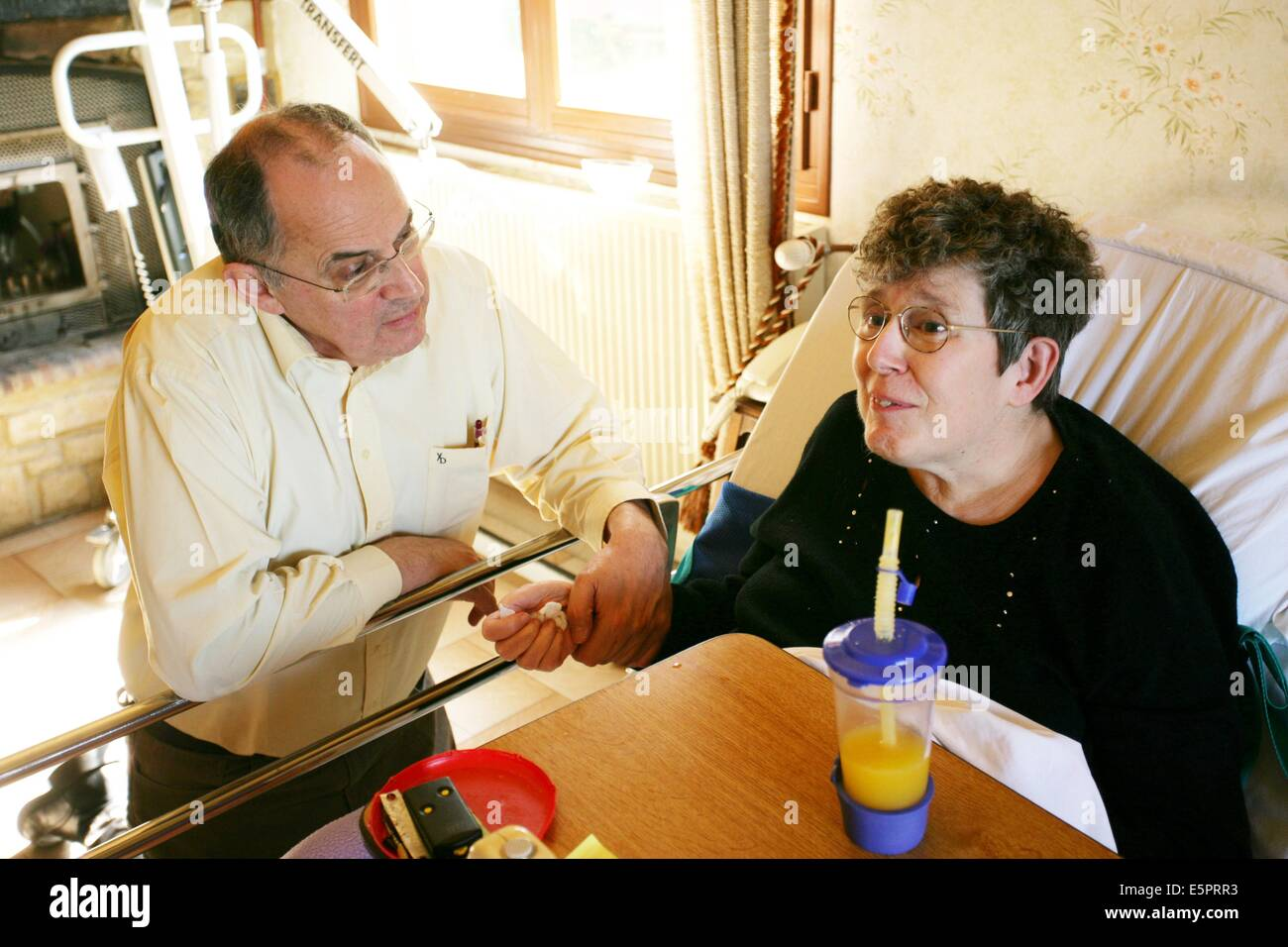 57 year old female patient suffering from multiple sclerosis (MS) receiving the visit of her general practitioner - Stock Image