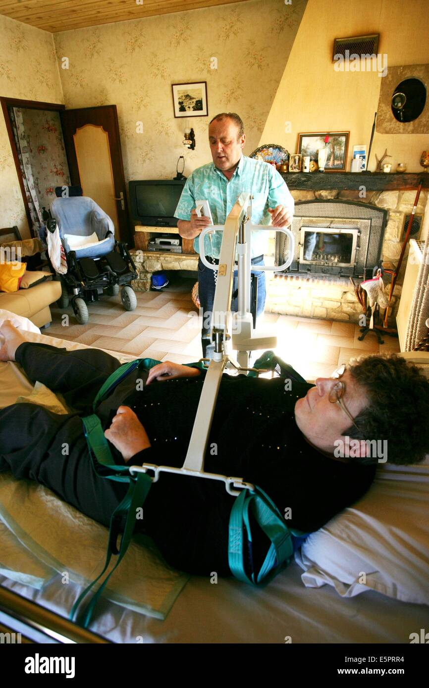 57 year old woman suffering from multiple sclerosis (MS), Her husband assists her in the everyday tasks, Here, he - Stock Image