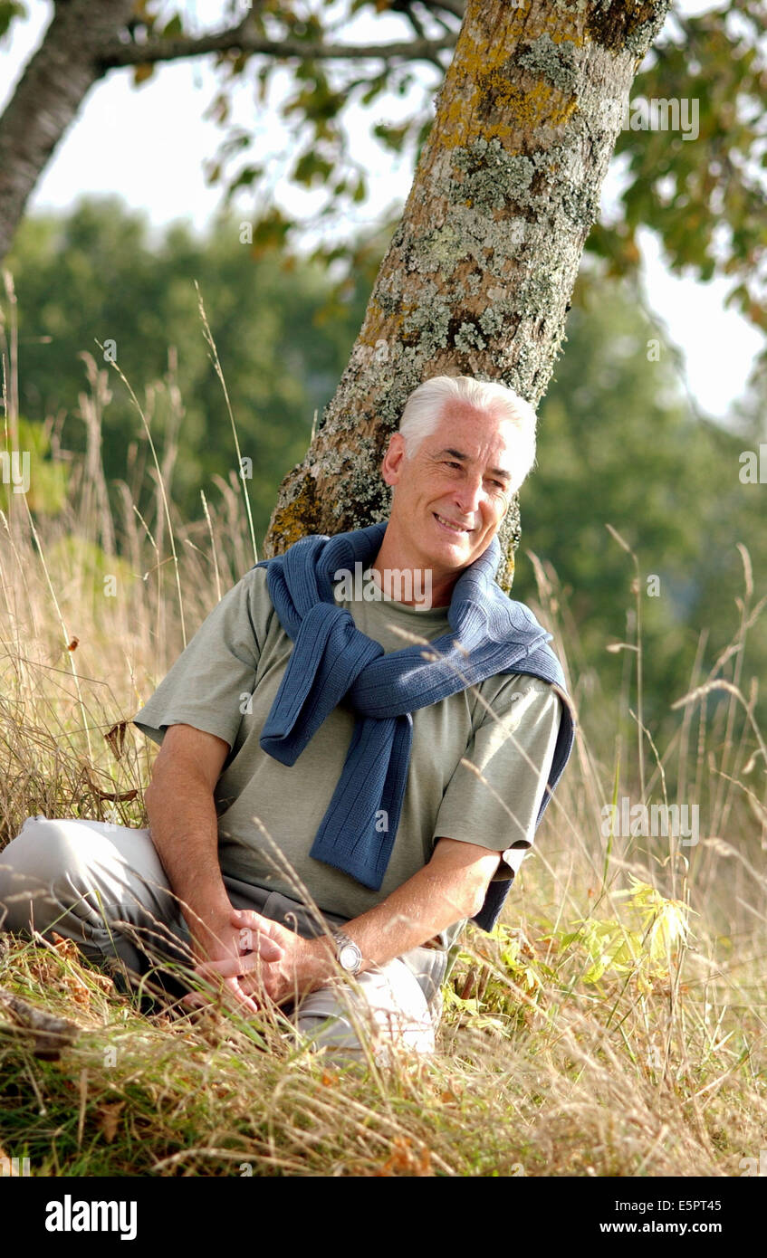 60-year-old man relaxing in the countryside. - Stock Image