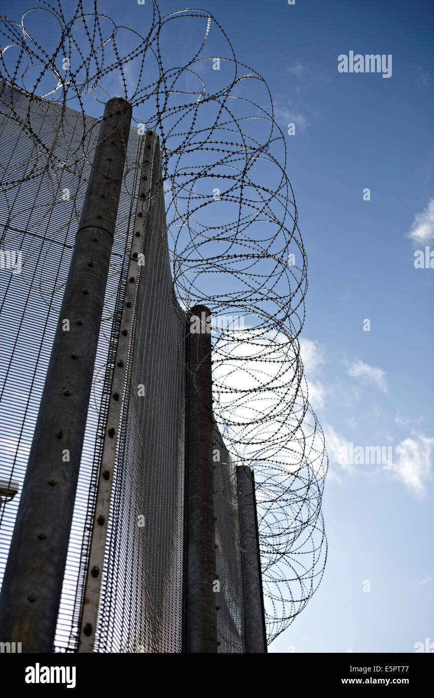 High security fencing, razor and barbed wire around the perimeter of a UK prison, containing criminals and asylum - Stock Image