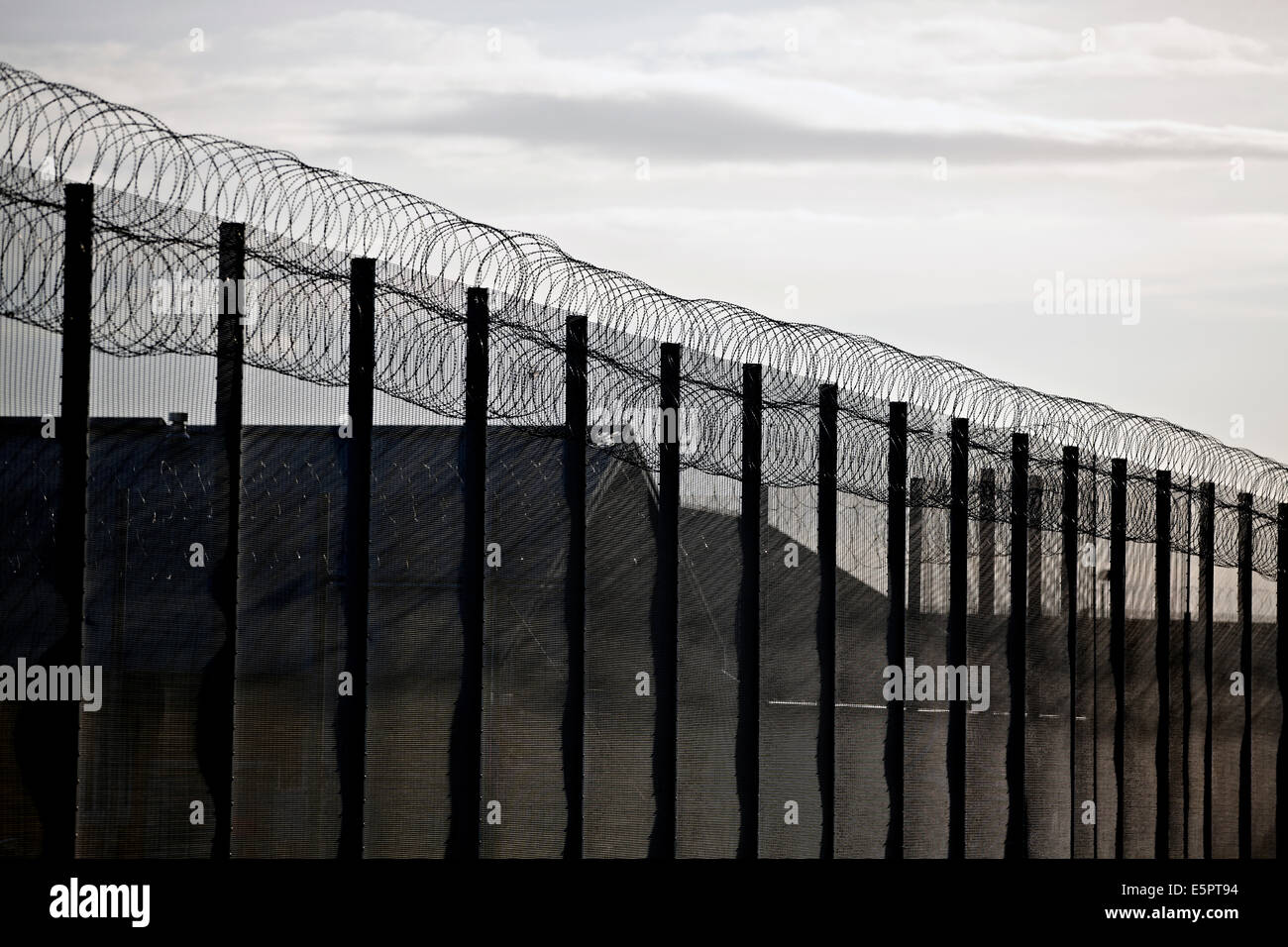 Security fencing, razor wire and CCTV cameras around the perimeter of a UK prison. - Stock Image
