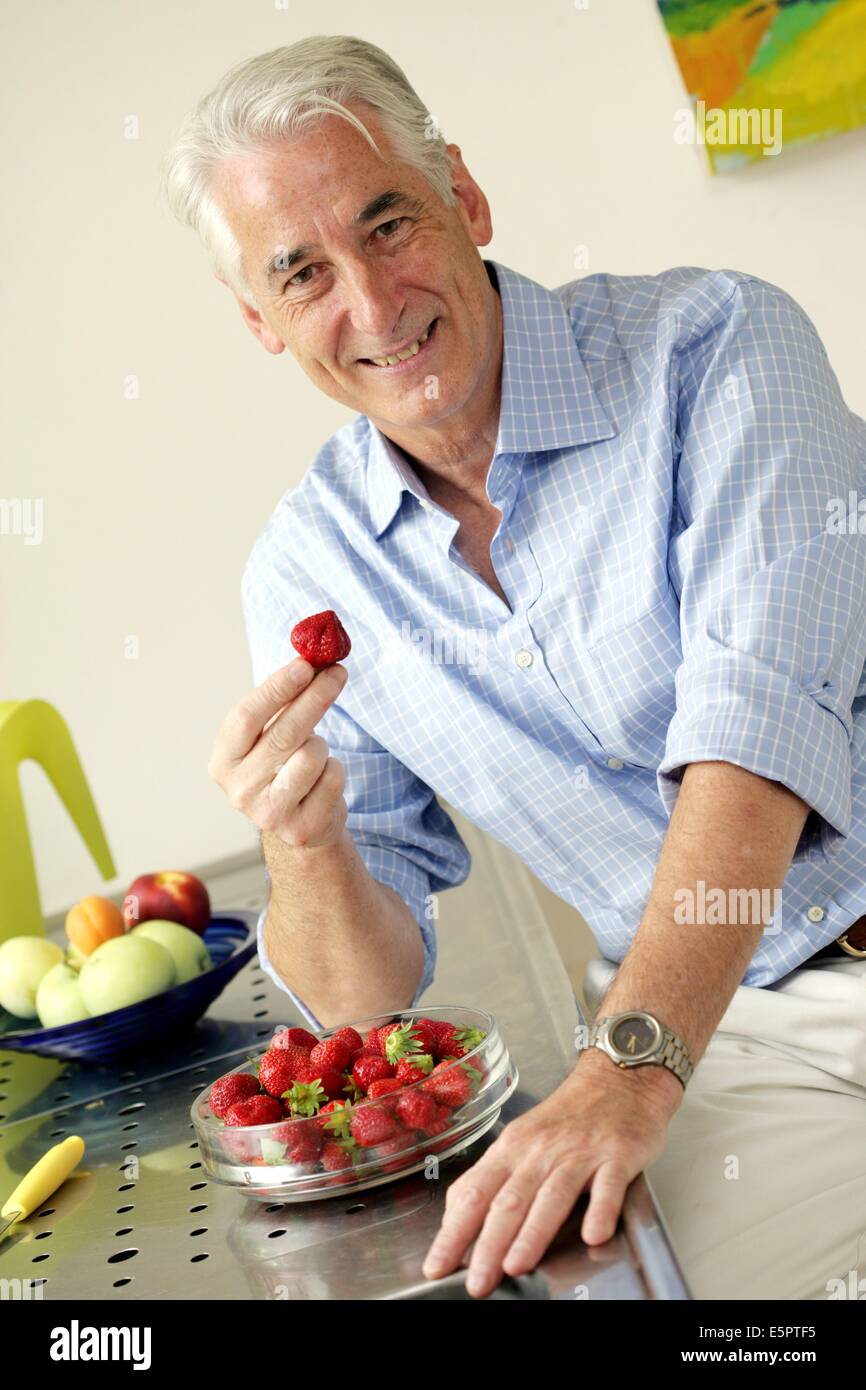 50-year-old man eating an strawberries. - Stock Image