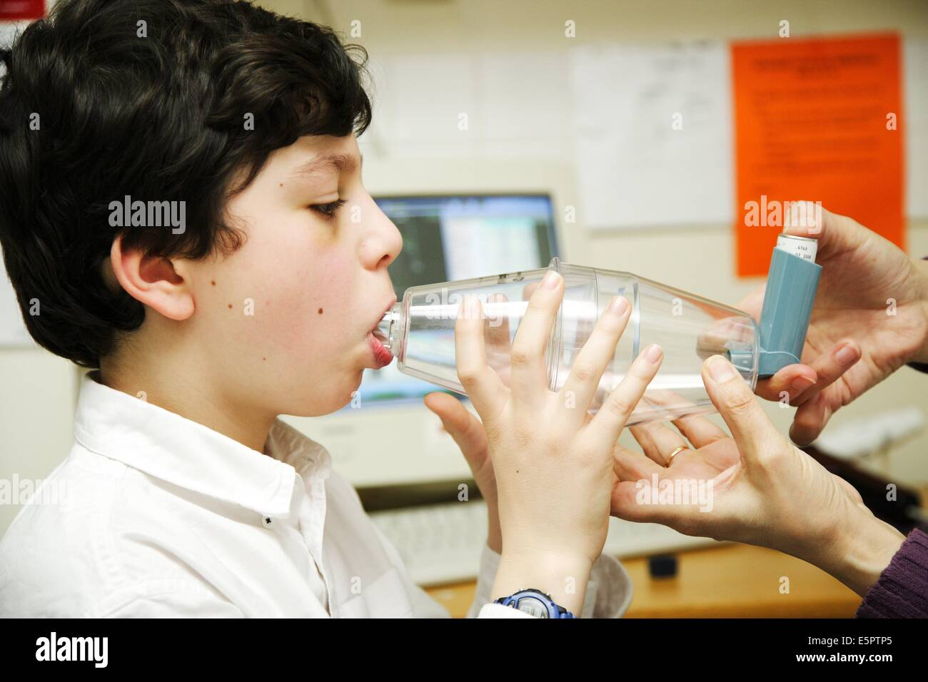 Asthmatic child inhaling bronchodilator aerosol with an inhalation chamber, Asthma center at the hospital Armand - Stock Image