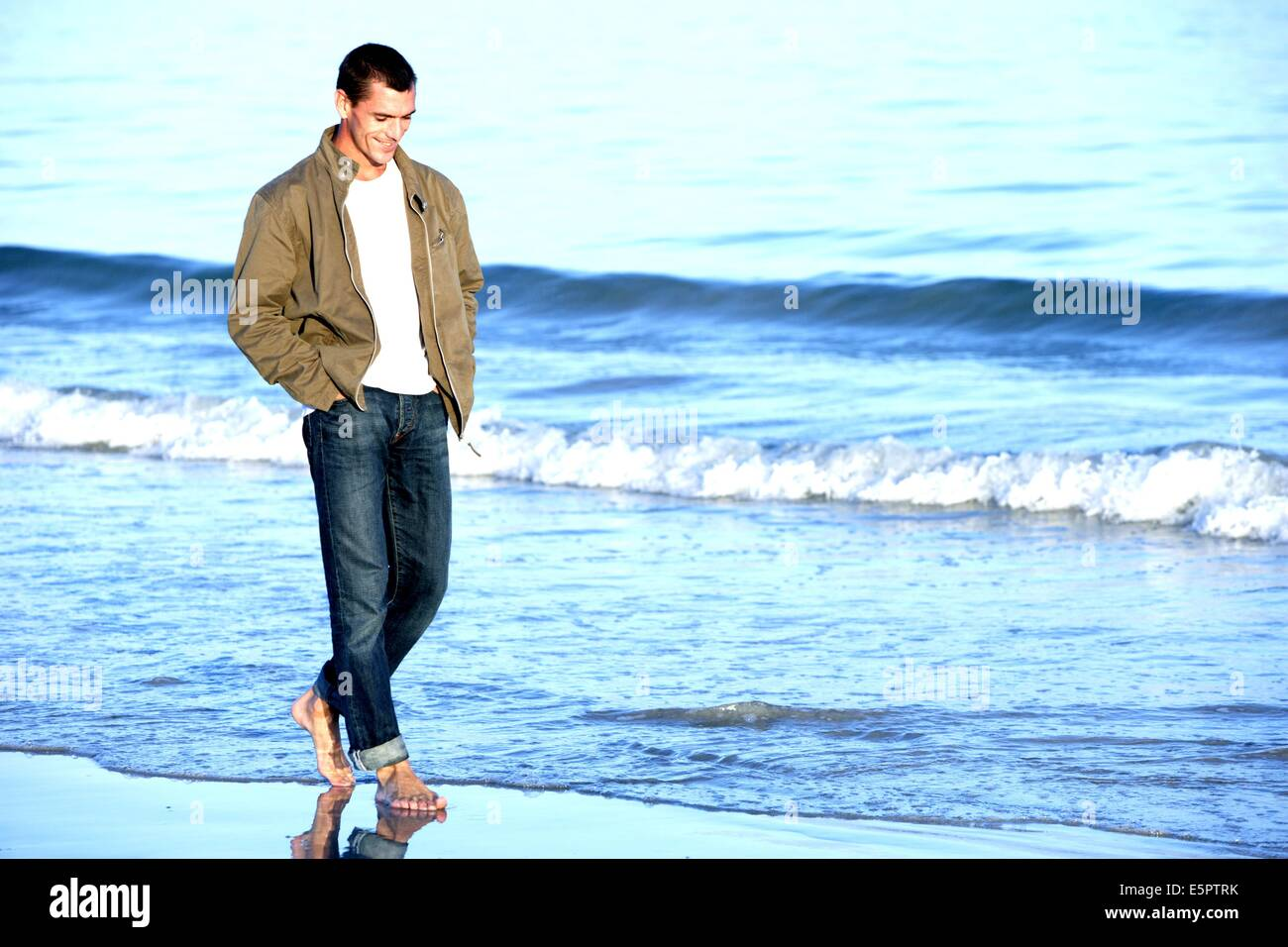 35-year-old man walking on the beach. - Stock Image
