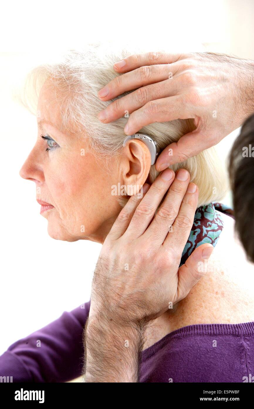 Hearing Aid Specialist Fitting Digital Hearing Aid To Elderly Woman Stock Photo Alamy