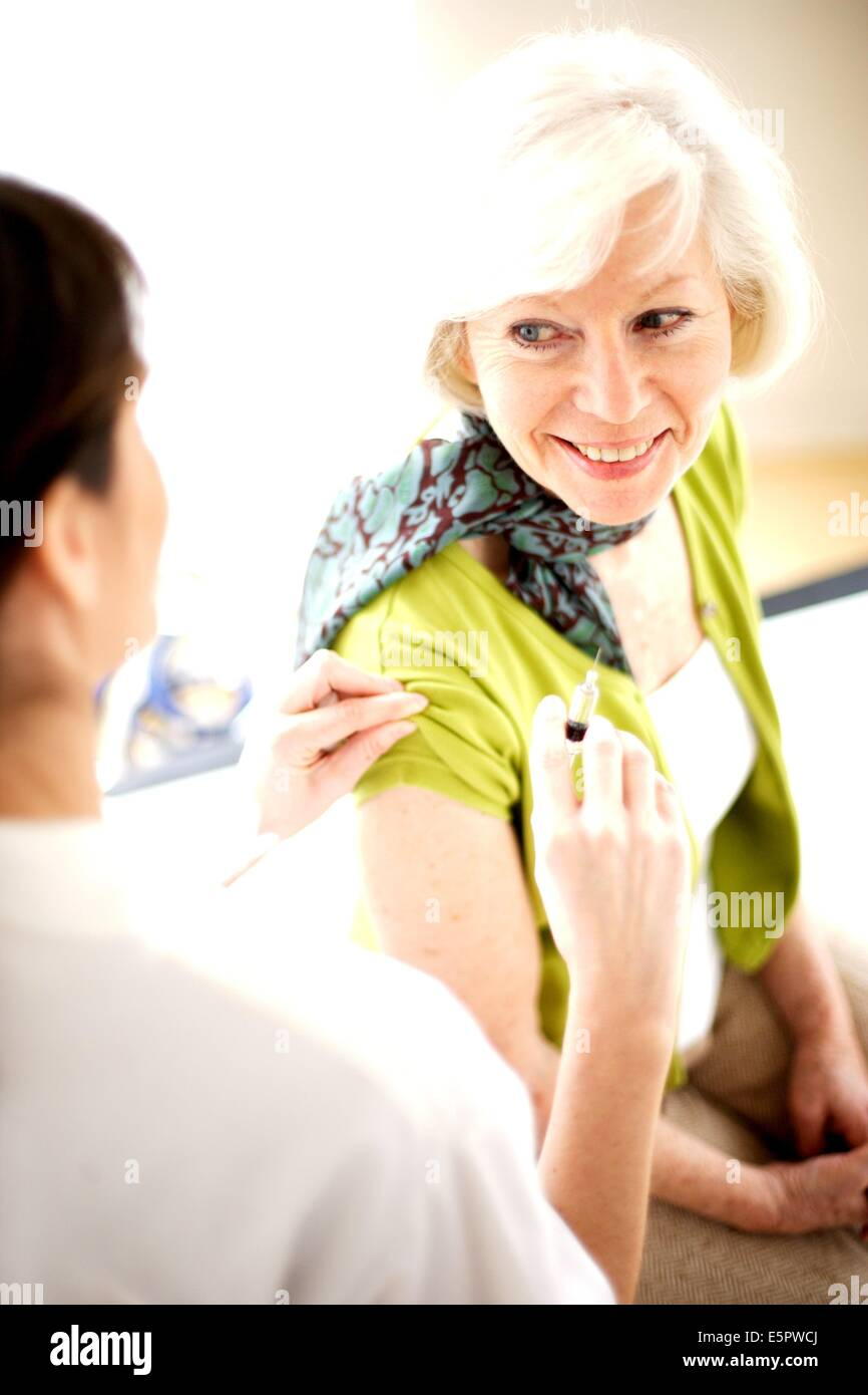 Elderly woman receiving vaccination against influenza. Stock Photo