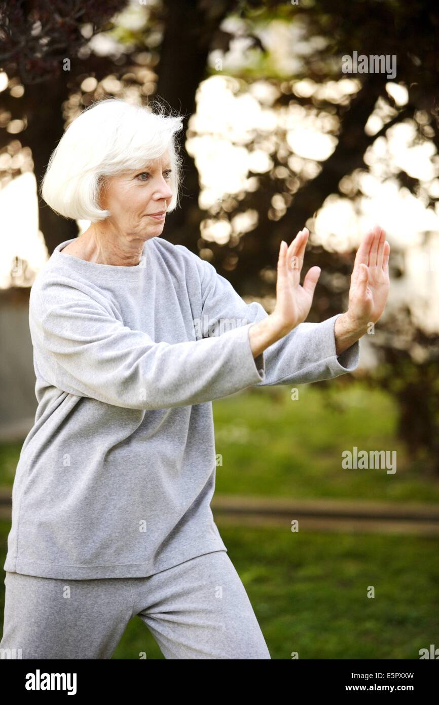 Elderly woman practising Tai chi. - Stock Image