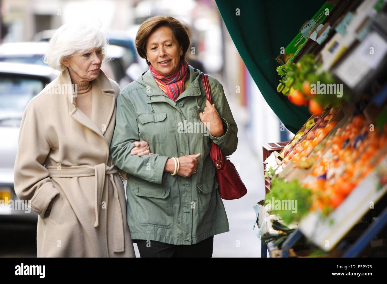 Woman and elderly woman walking in the street. - Stock Image