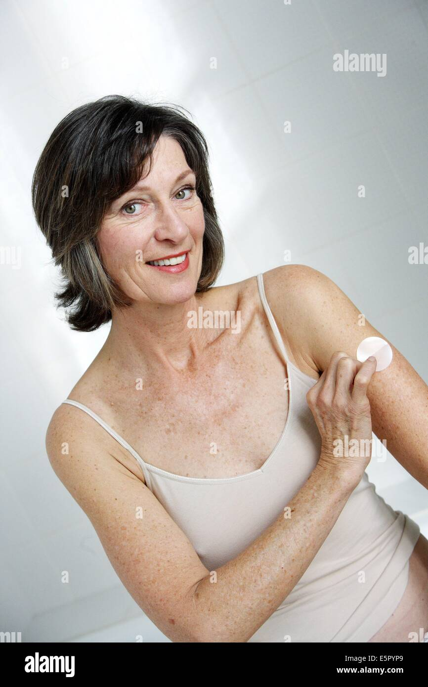 Senior woman using an oestrogen patch for a Hormone Replacement Therapy, in order to releive the undesirable effects - Stock Image