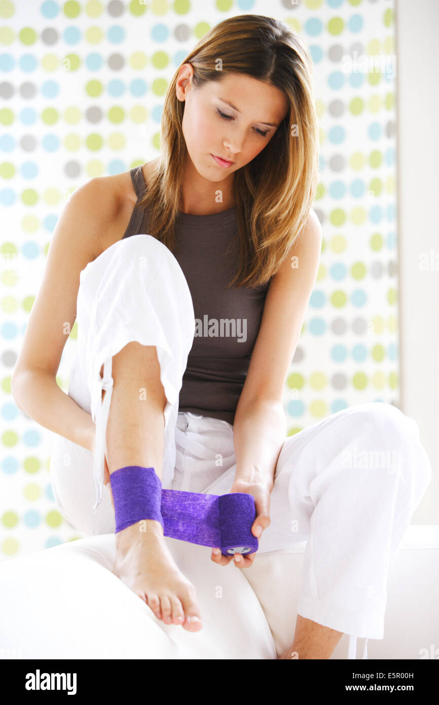 Woman with sprain to her ankle applying bandage. - Stock Image