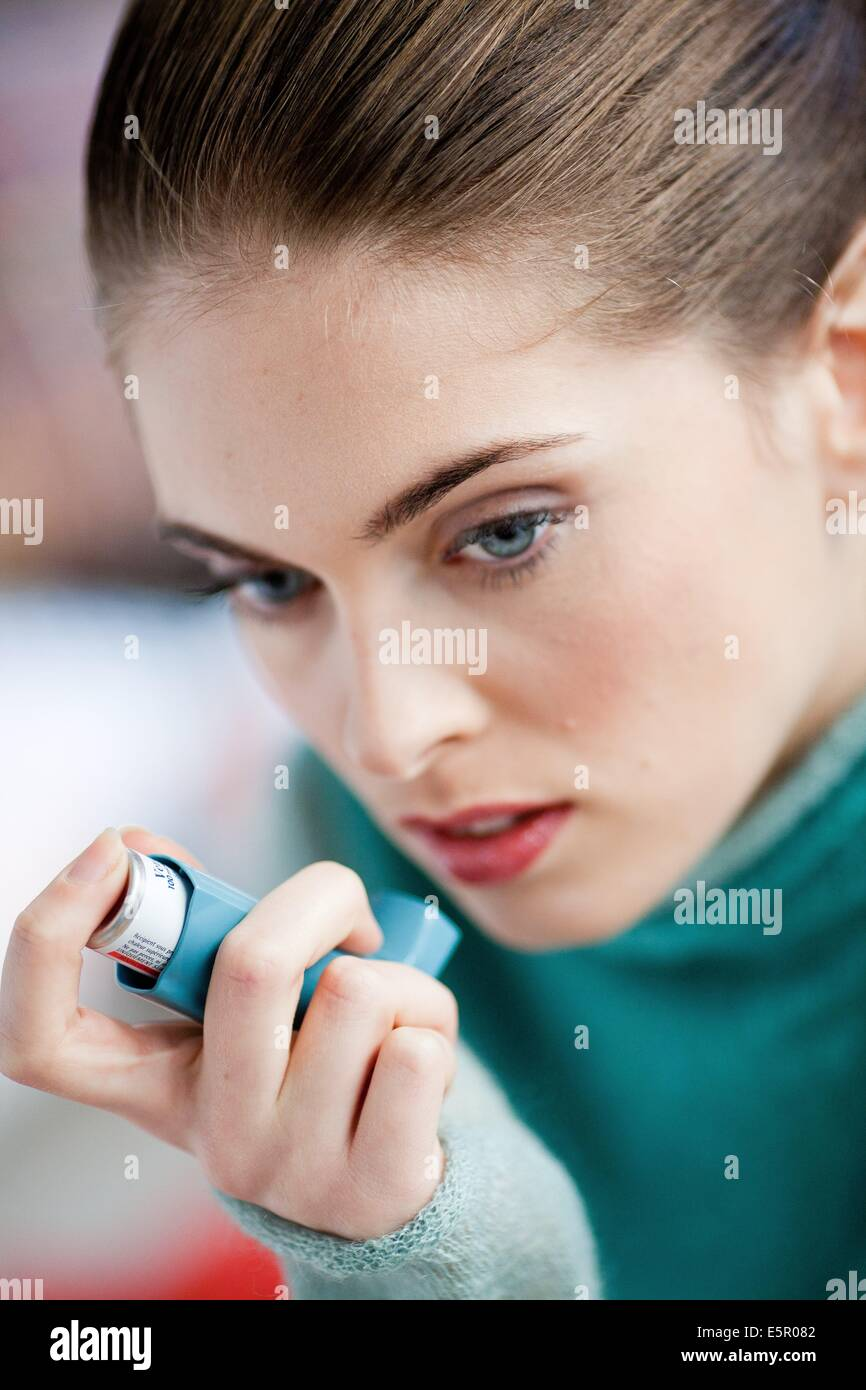 Woman using an aerosol inhaler that contains bronchodilator for the treatment of asthma. The inhaler dilates lungs - Stock Image