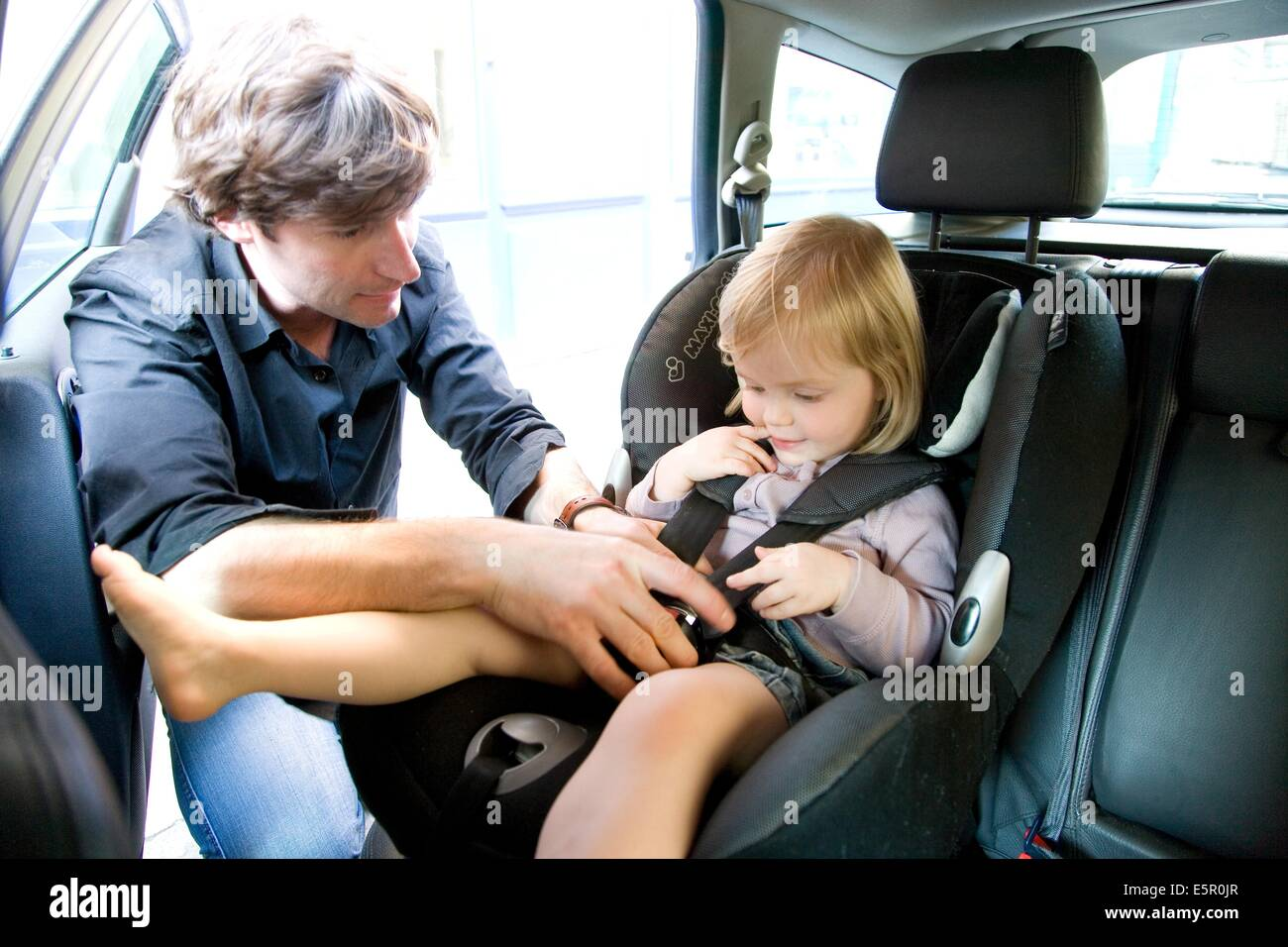 father securing his 2 year old baby girl in a baby car seat stock photo 72420175 alamy. Black Bedroom Furniture Sets. Home Design Ideas