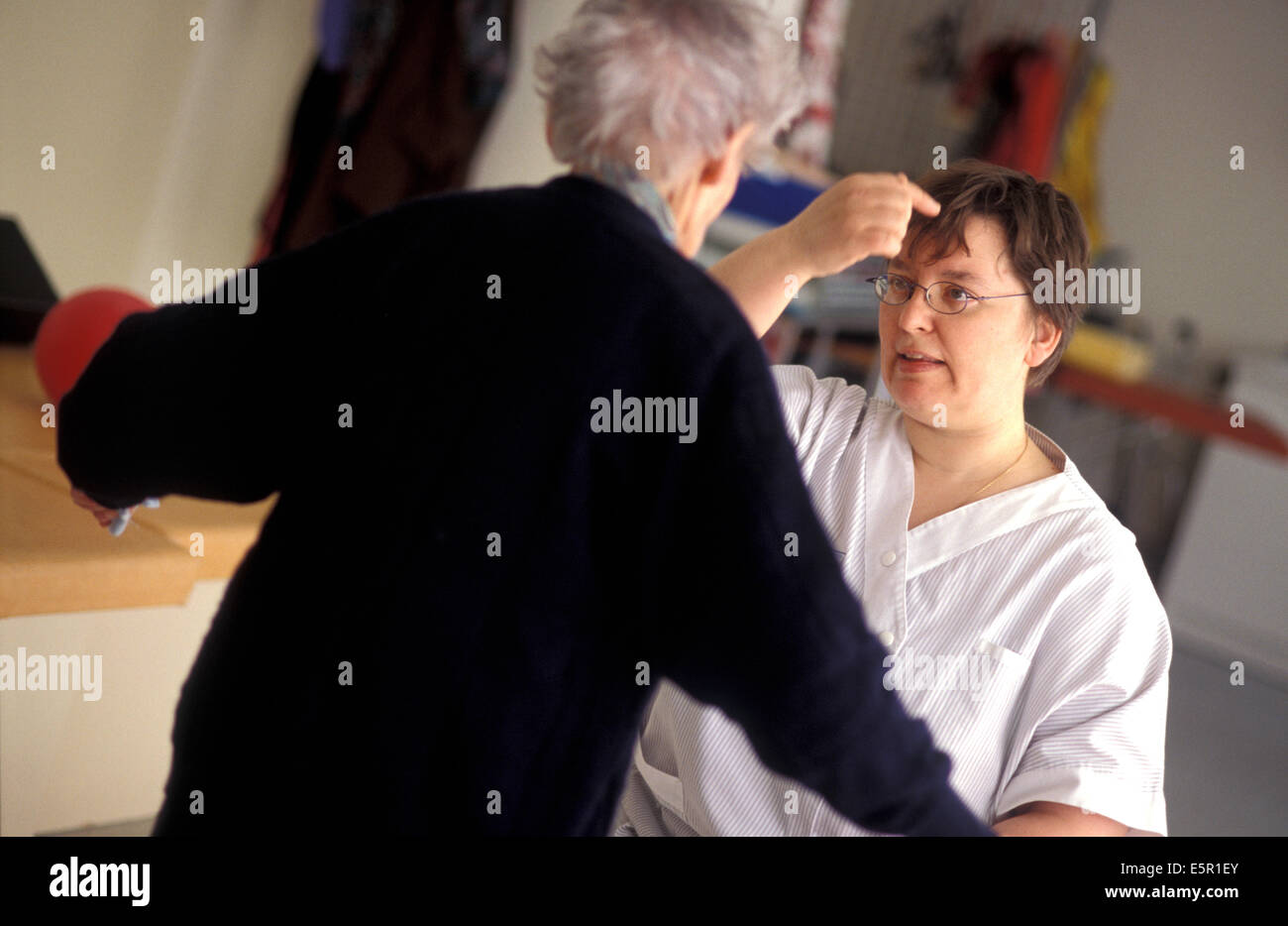 Elderly person doing functional rehabilitation exercises with a physiotherapist, Alzheimer unit of the Geriatrics - Stock Image