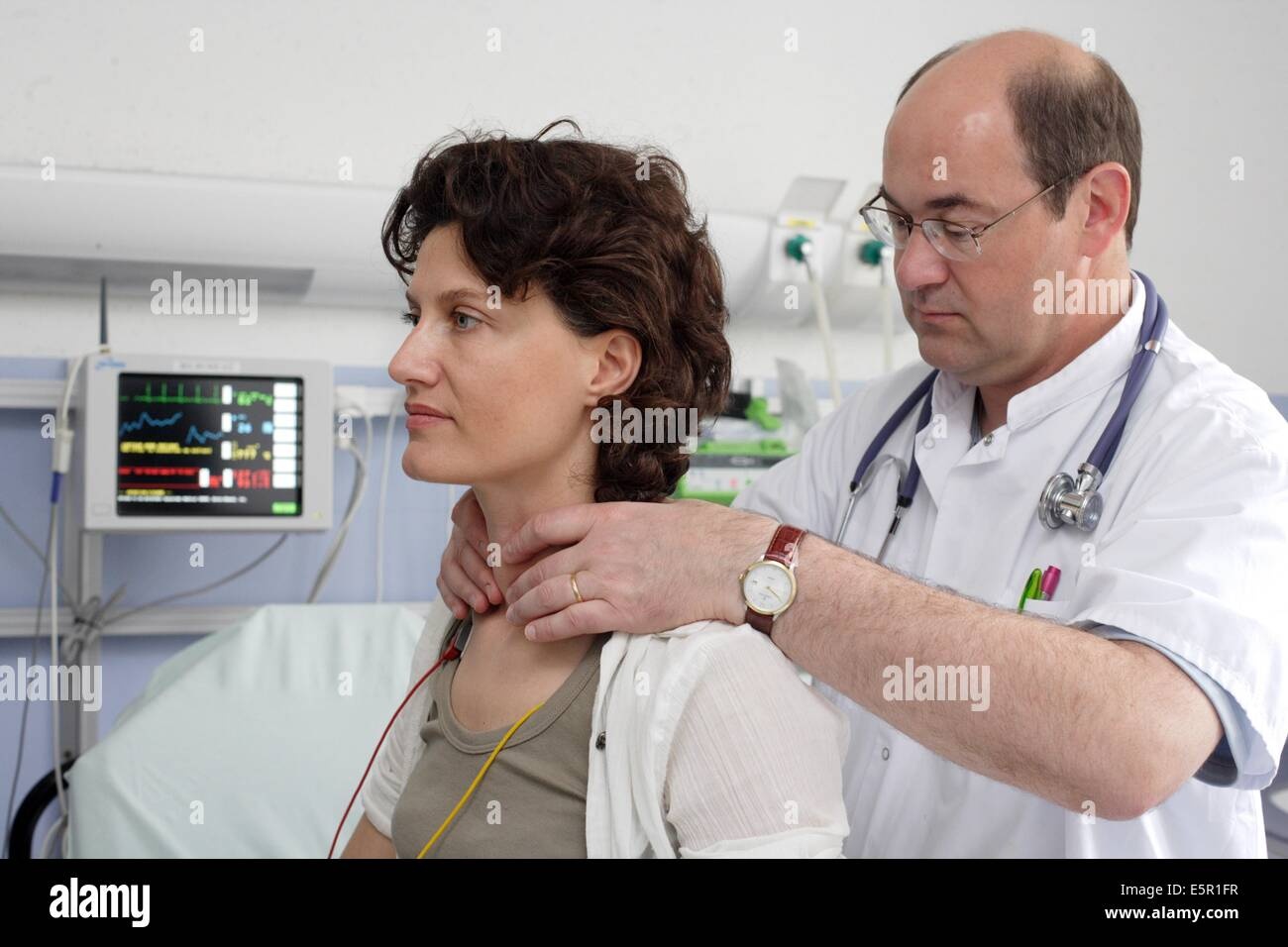 Hospital doctor examining the thyroid gland of a patient at emergency department. - Stock Image