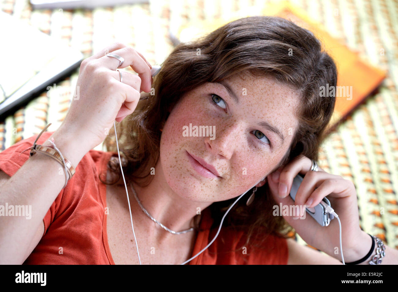 Teenage girl listening music with mp3 player. - Stock Image