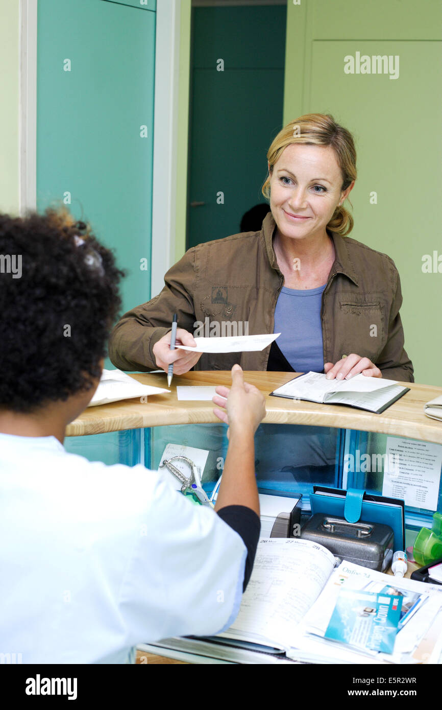 Woman paying doctor's fees to a medical secretary of a medical office. - Stock Image