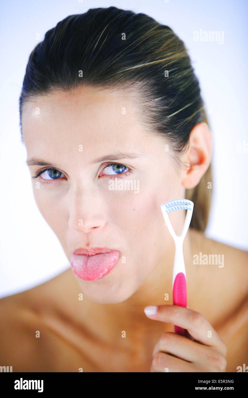 Woman brushing her tongue with a specific tongue-brush to eliminate the bacteria responsible for bad breath. - Stock Image