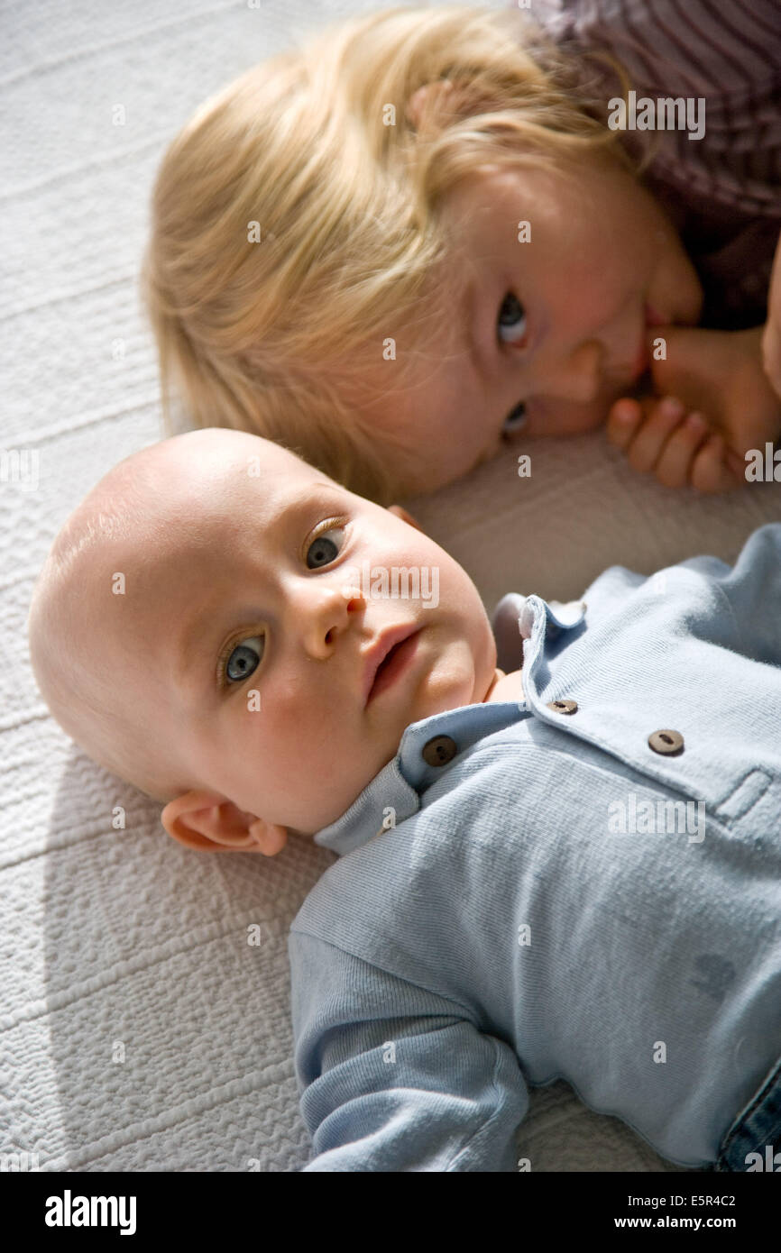 9 month old baby with his sister stock image