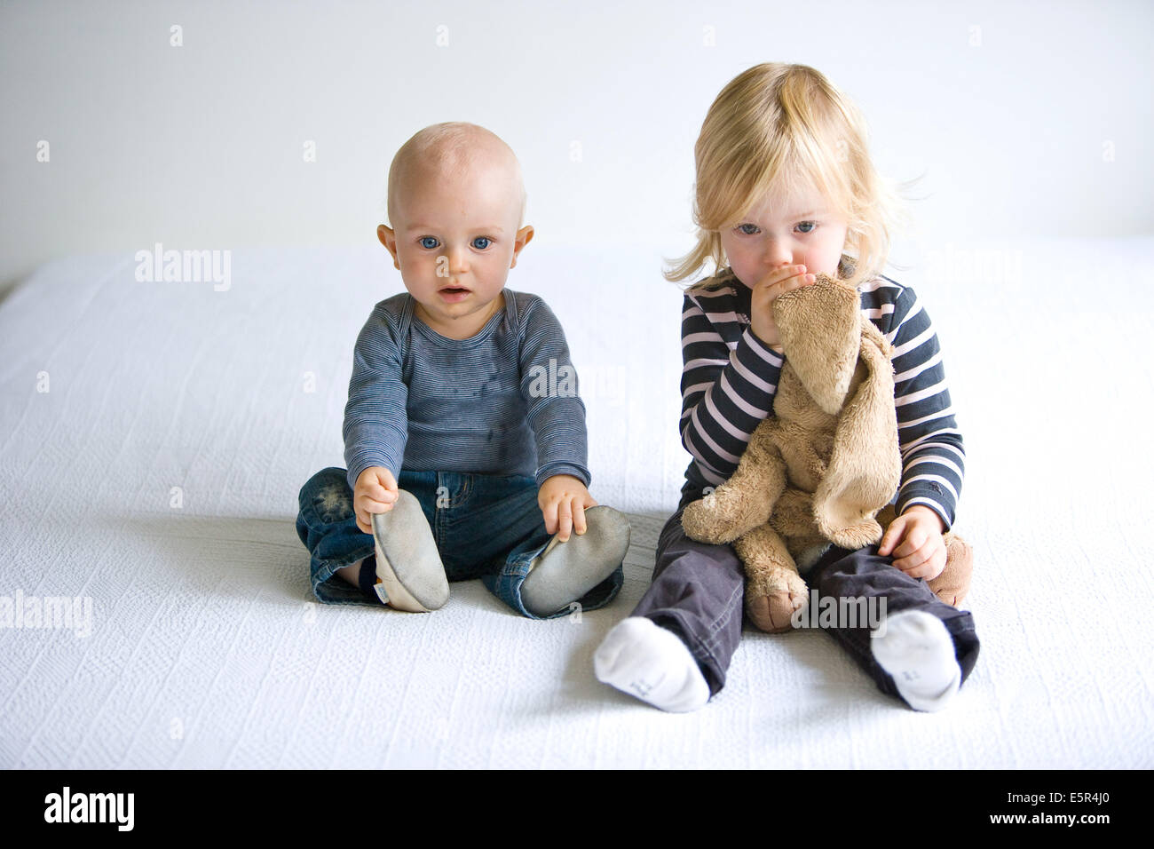 Brother and sister of 9 and 30 month old watching television stock image