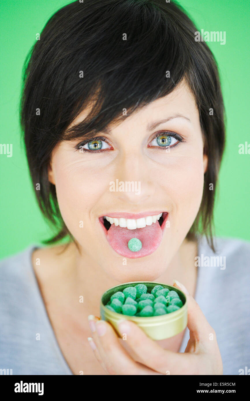 Woman taking lozenge for sorethroat. - Stock Image