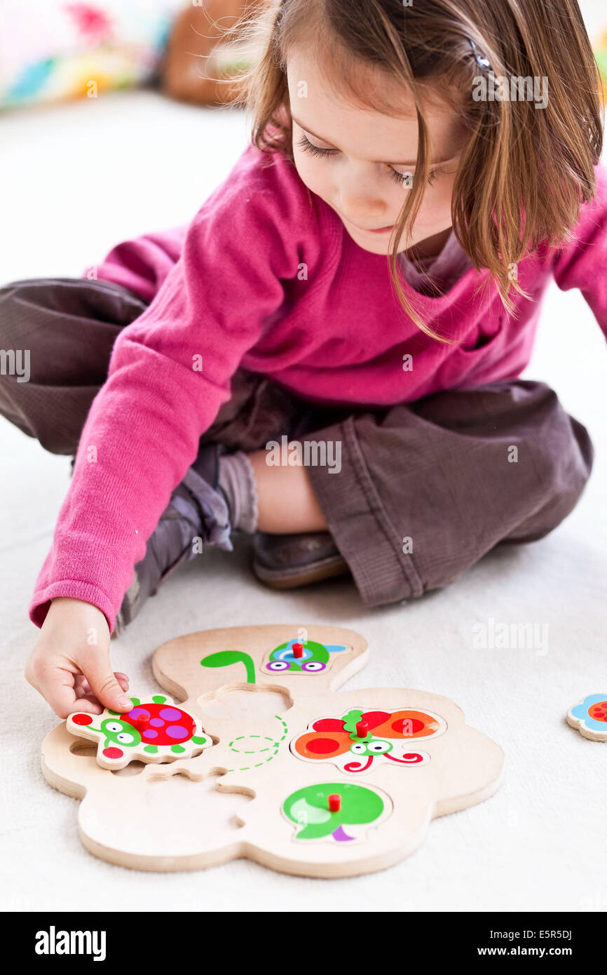 4-year-old girl playing with an educational puzzle. - Stock Image