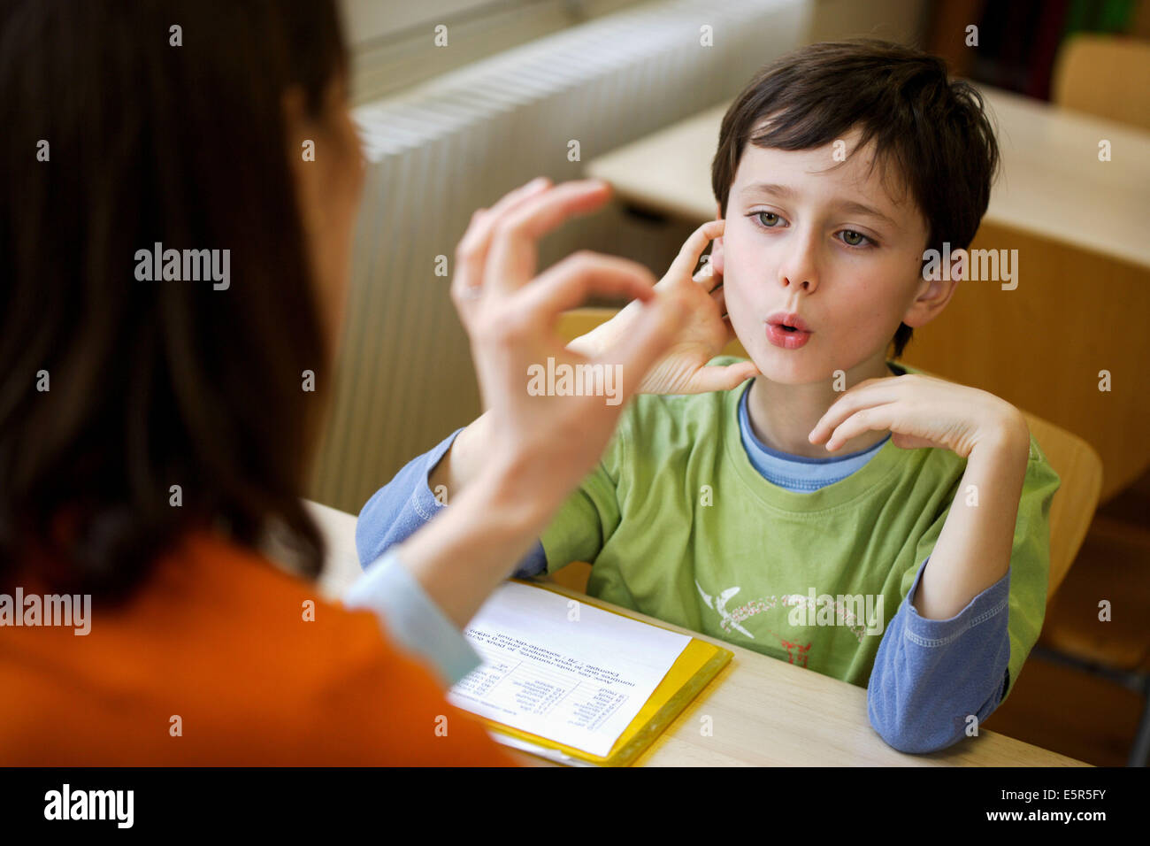 8 year old boy during speech therapy session. - Stock Image