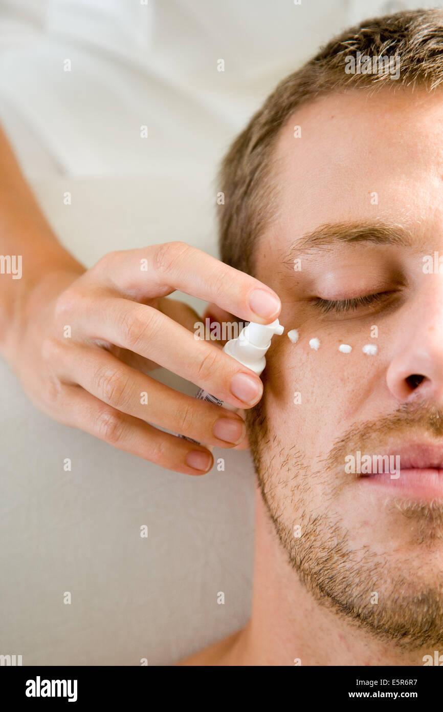 Man receiving an anti-wrinkle or anti-pocket cream around the eyes. - Stock Image
