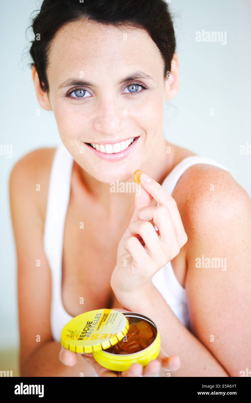Woman taking lozenge. - Stock Image