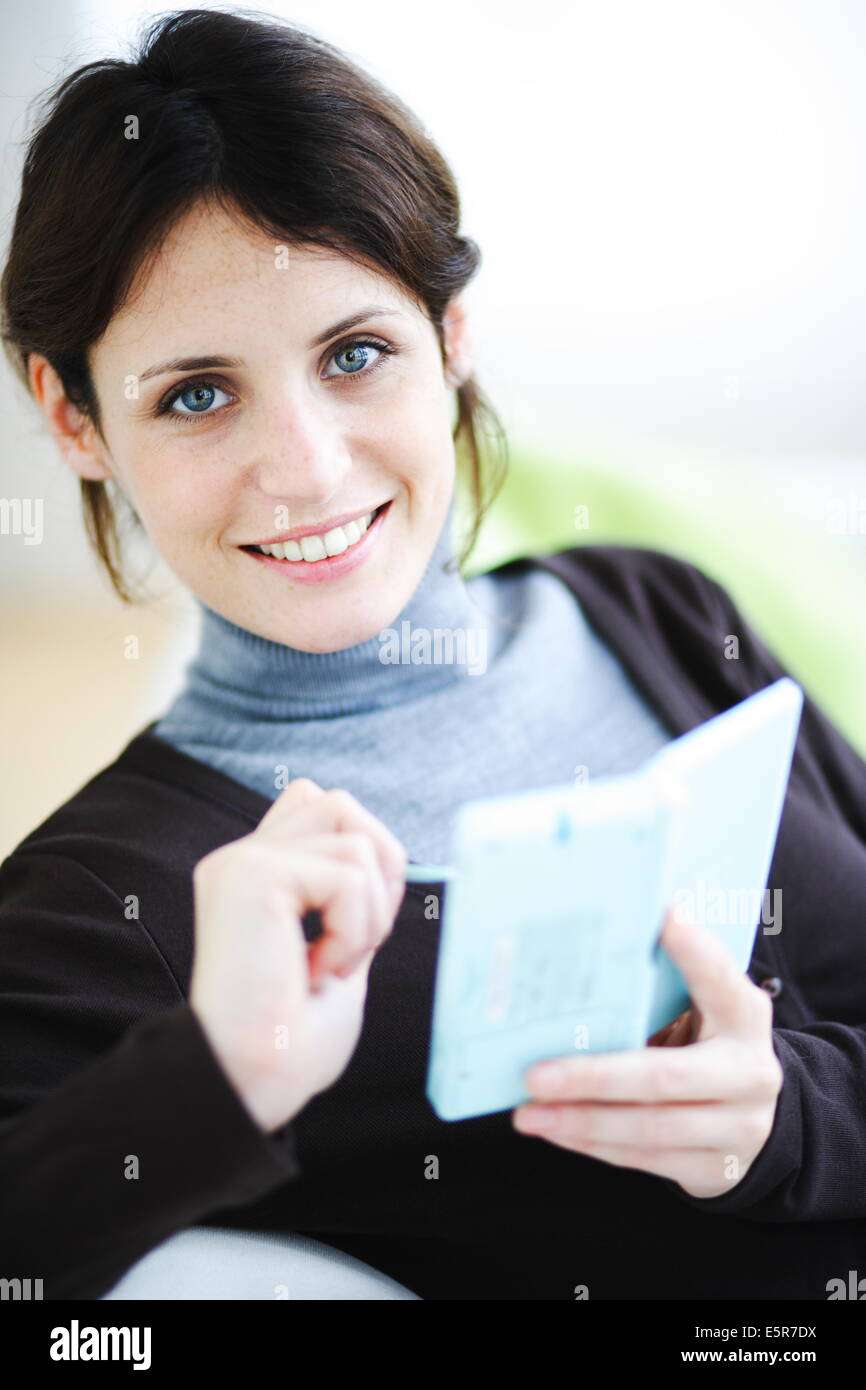 Woman playing with a video game console. - Stock Image